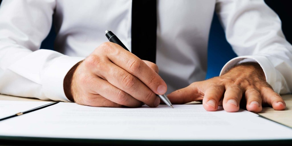 Business man signing documents - Canadian Mortgage Pros